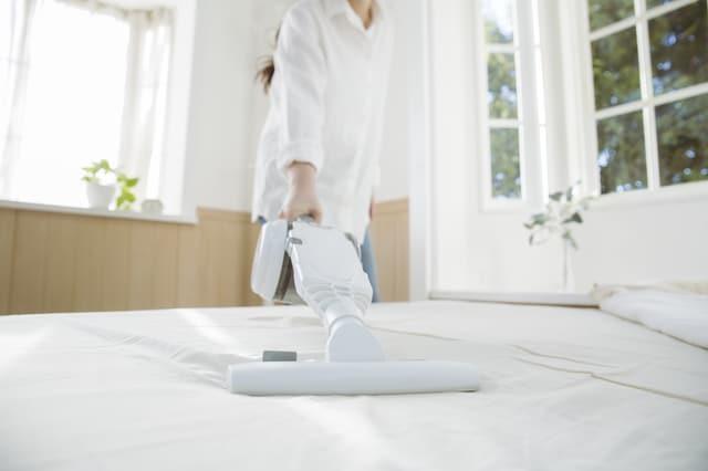 布団に掃除機をかける女性