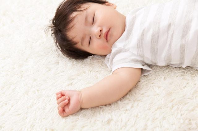 カーペットの上で寝る赤ちゃん