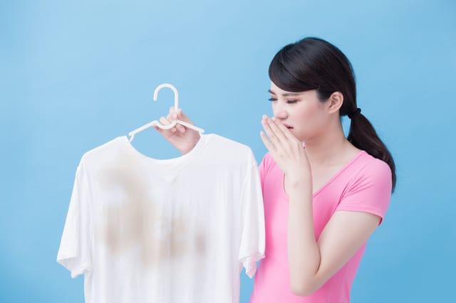 汚れたシャツを持つ女性