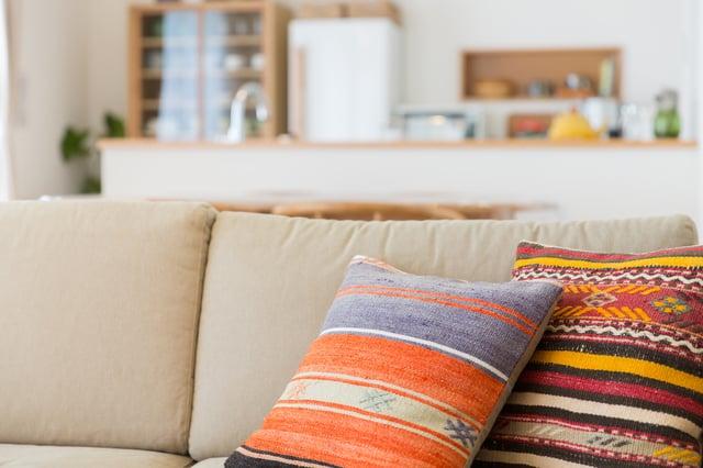 オレンジのクッションとソファ