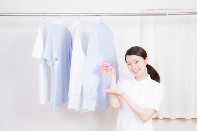 消臭剤を服にかける女性