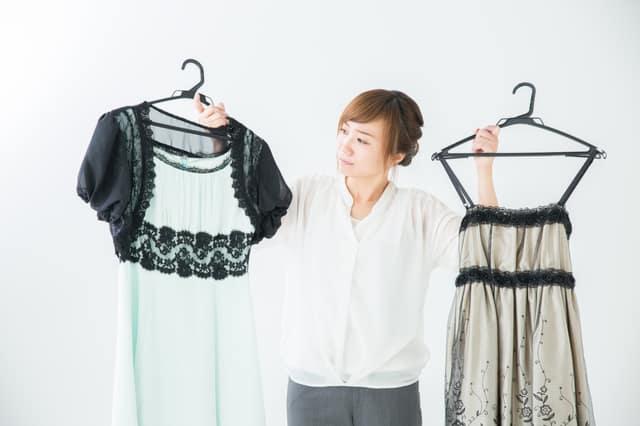 2つのドレスで悩む女性