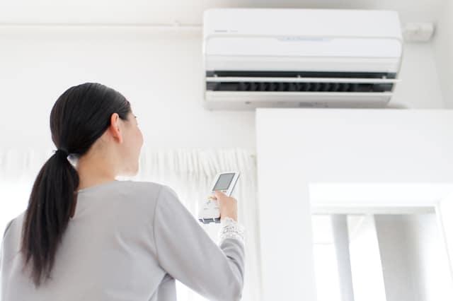 エアコンのスイッチを入れる女性
