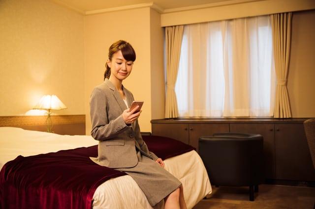 ビジネスホテルでスマホを見る女性