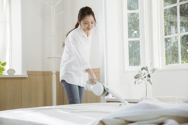 布団掃除機を使う女性