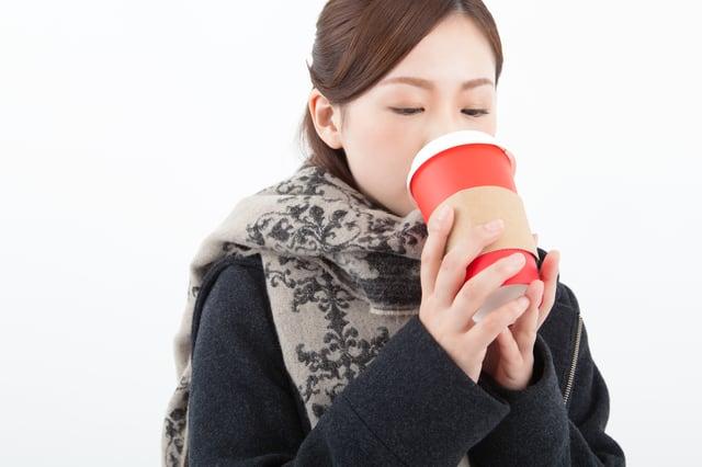 マフラーを巻いてコーヒーを飲む女性