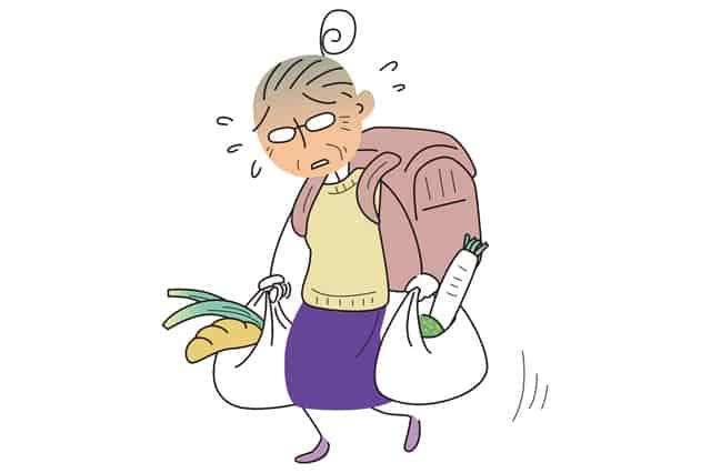 重い荷物を抱える高齢者