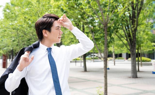 汗をふくスーツ姿の男性