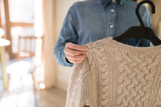 自宅でセーターを洗濯する女性