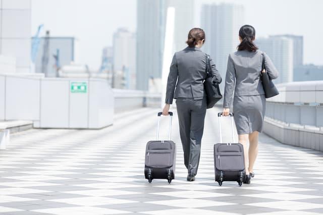 キャリーケースを引くスーツ姿の女性