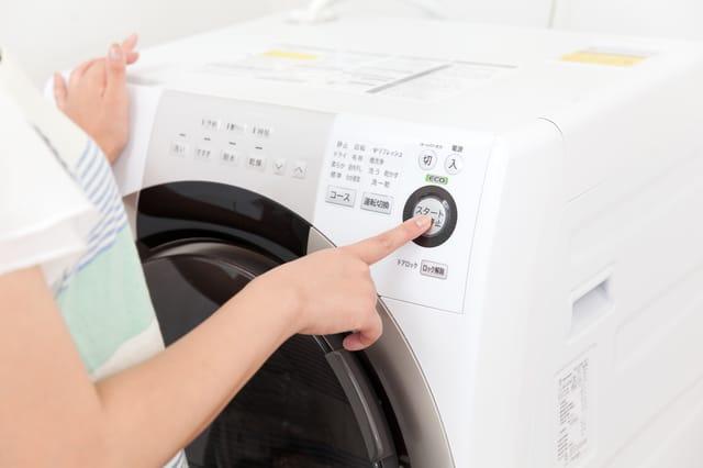 洗濯機を稼働させる女性