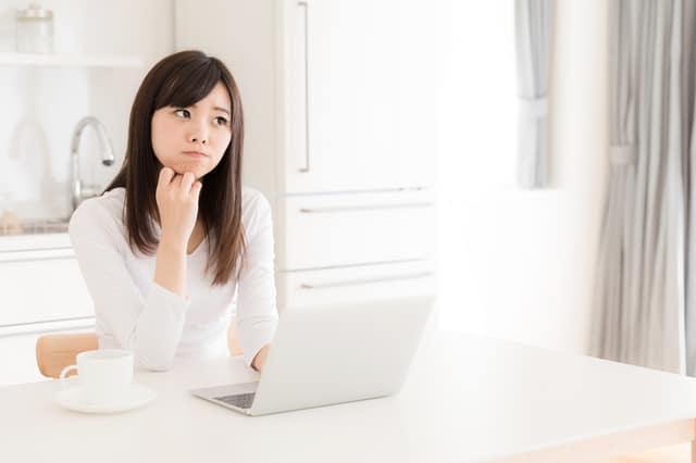 パソコンに向かって悩む女性