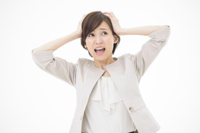 スーツを着て頭を抱える女性