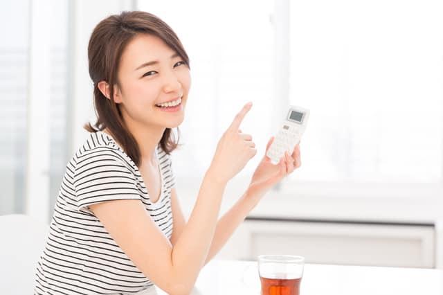 電卓を持って笑顔の女性